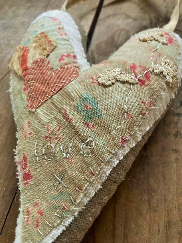 Hand stitched valentine heart with early and old fabric and lace close up of details