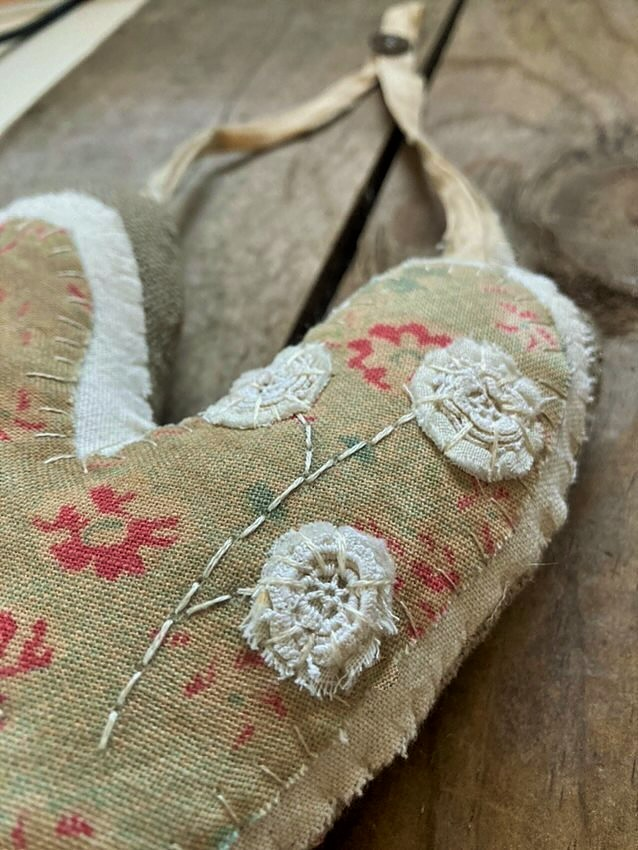 Details of my hanging hand stitched valentine heart with early textiles- Pincushion Flower