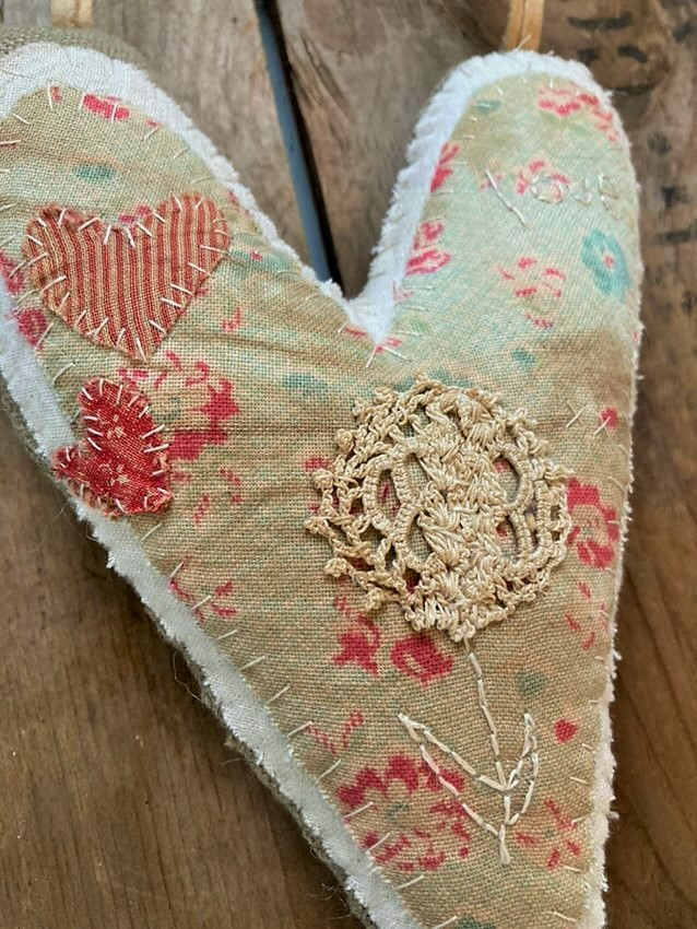 Hand stitched valentine heart with early and old fabric and lace close up of details and early lace
