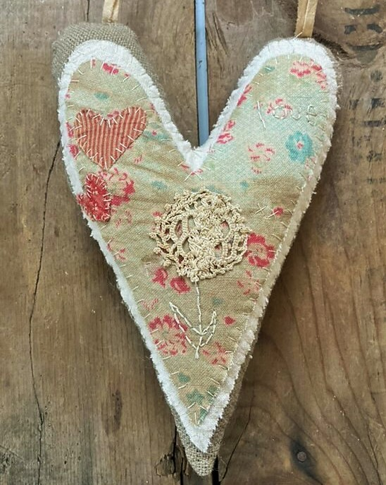 Hand stitched valentine heart with early and old fabric and lace to hanging pincushion