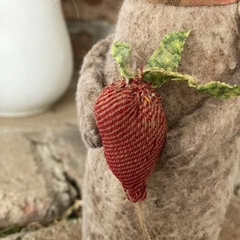 Little handmade rabbit holding a radish made with antique textiles