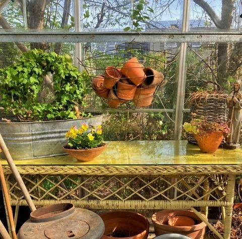 vintage yellow wicker table and old terracotta pots
