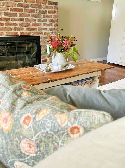 Fresh flowers arranged in vintage Ironstone, handmade linen pumpkins, and pretty floral and velvet pillows create a lot of textures for fall decorating